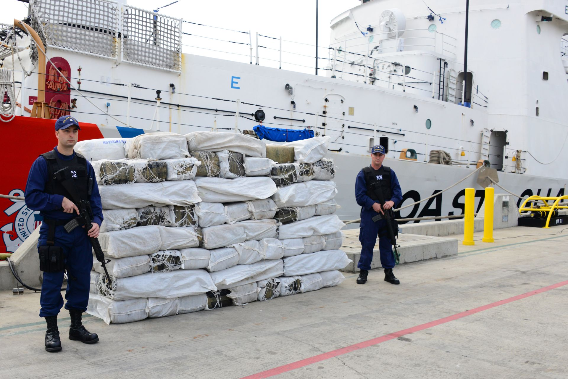 Crewmen from Seattle-based Coast Guard Cutter Mellon stand guard near 3,500 pounds of marijuana the crew offloaded from the cutter at Naval Base San Diego, Jan. 8, 2014. The Mellon's crew, along with the crews of San Diego-based Coast Guard Cutter Sea Otter, a Sacramento-based Coast Guard C-130 Hercules aircraft and a Customs and Border Protection Office of Air and Marine aircraft, interdicted the marijuana and more than 30 pounds of methamphetamine, and detained four suspected smugglers from a panga boat in international waters approximately 170 miles southwest of San Diego, Jan. 3. (U.S. Coast Guard photo by Petty Officer 3rd Class Connie Gawrelli)
